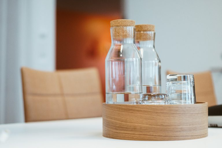 Water carafes with drinking glasses in a wooden serving tray on a conference table at Nemely's Stockholm office