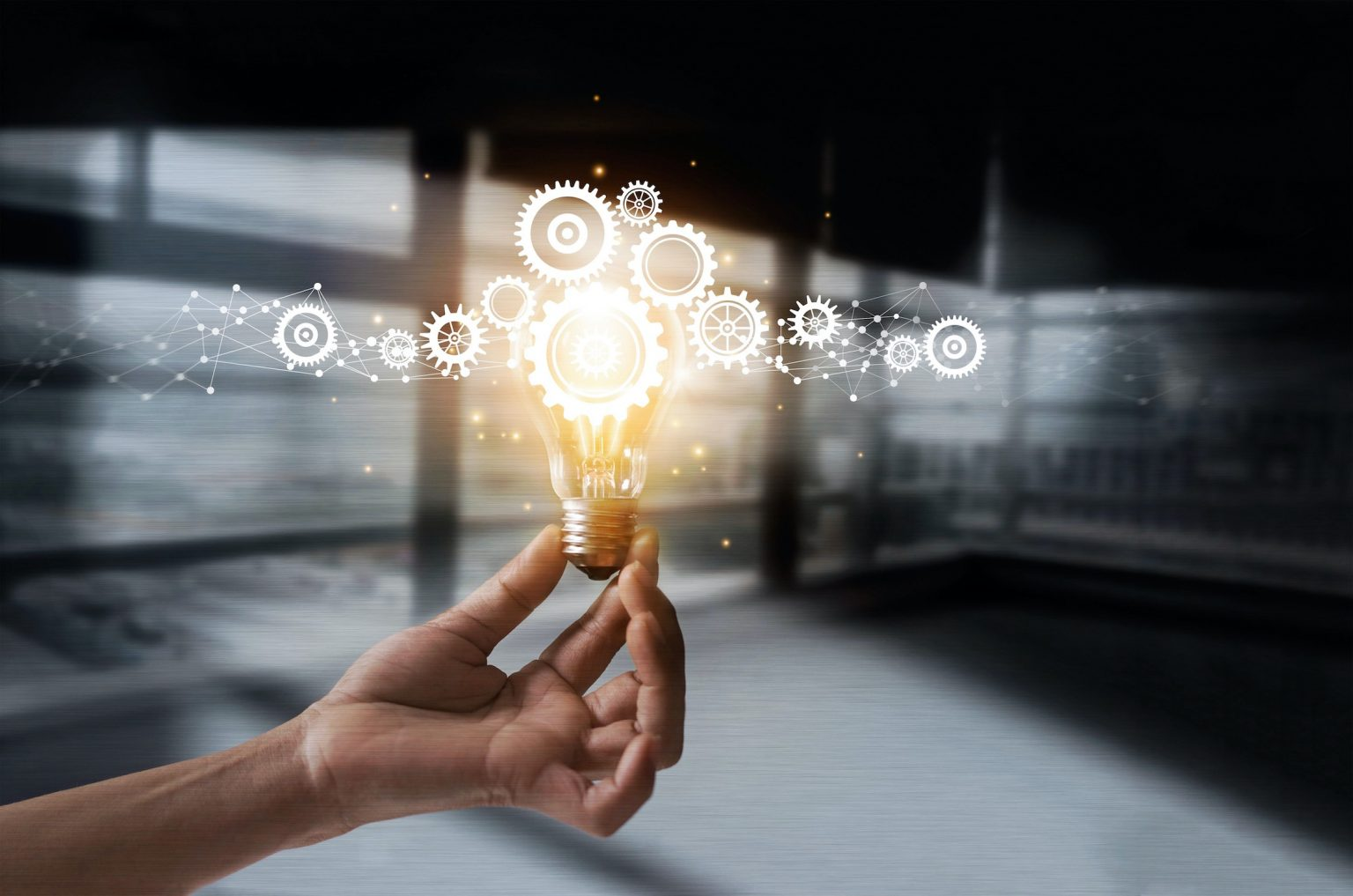 A hand holding a light bulb with cogs and gears on it symbolizing ideas and solutions