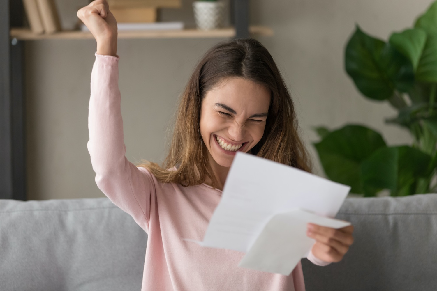 A happy lady holding and looking at a paper document with one hand and another hand with closed fist
