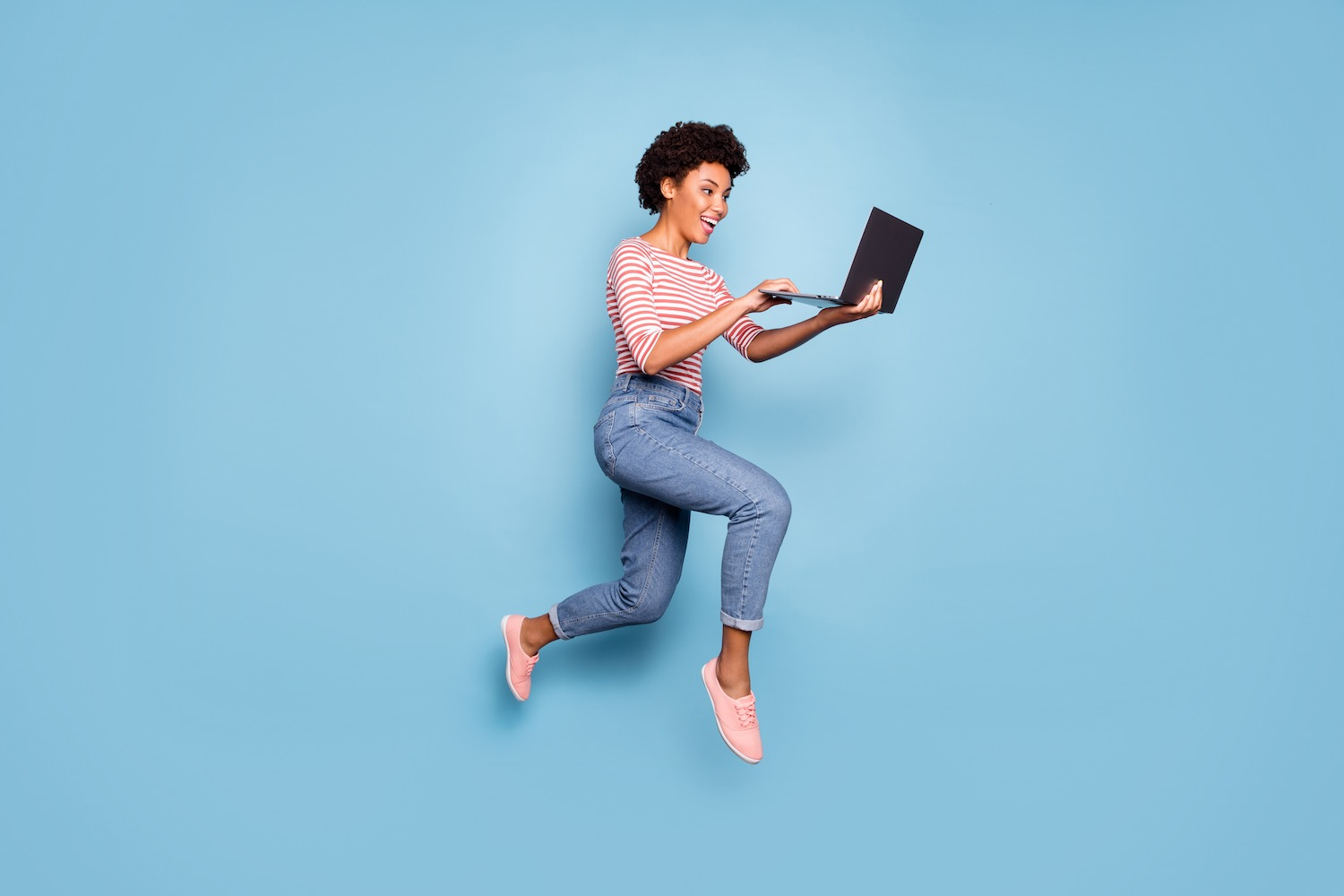 A woman hopping while holding a laptop in front of a blue background