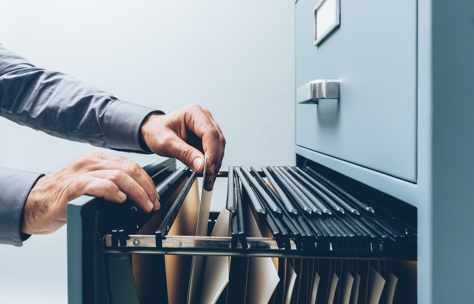 Two hands holding a folder document from filing or storage cabinet drawer
