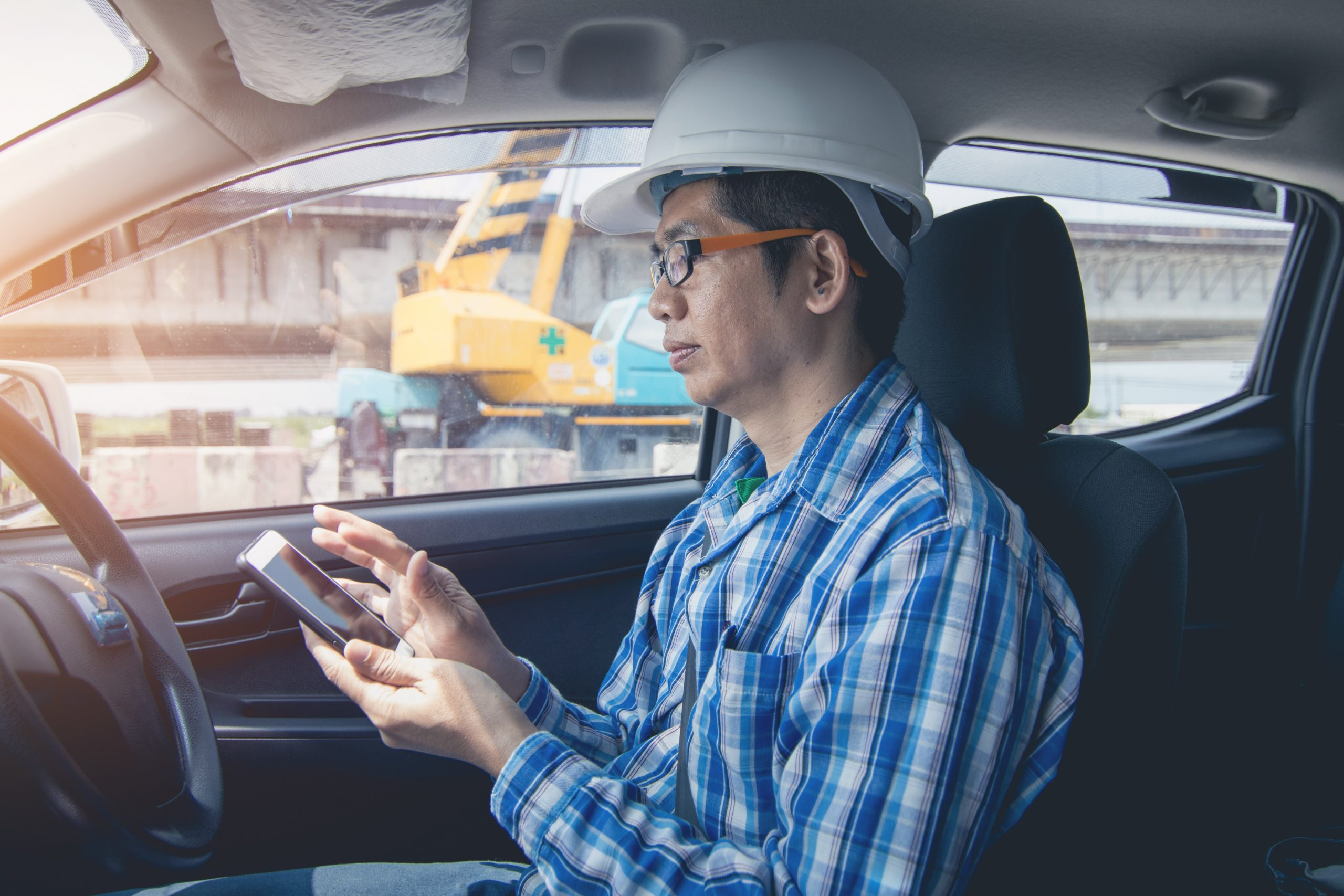 A field staff employee inspecting the optimized and planned routes on a mobile device while in a work vehicle