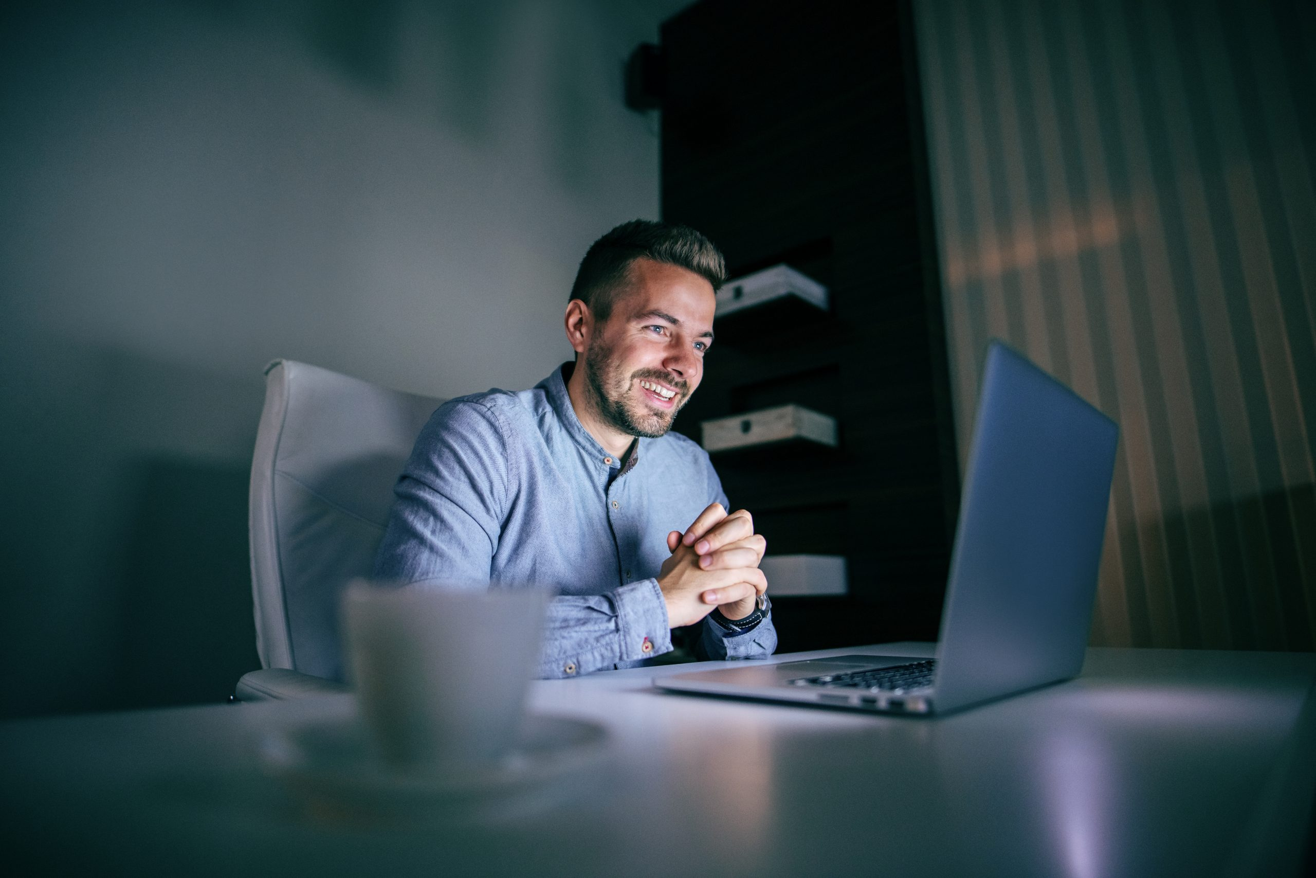 A productive businessman sitting and looking at a laptop with a happy demeanour