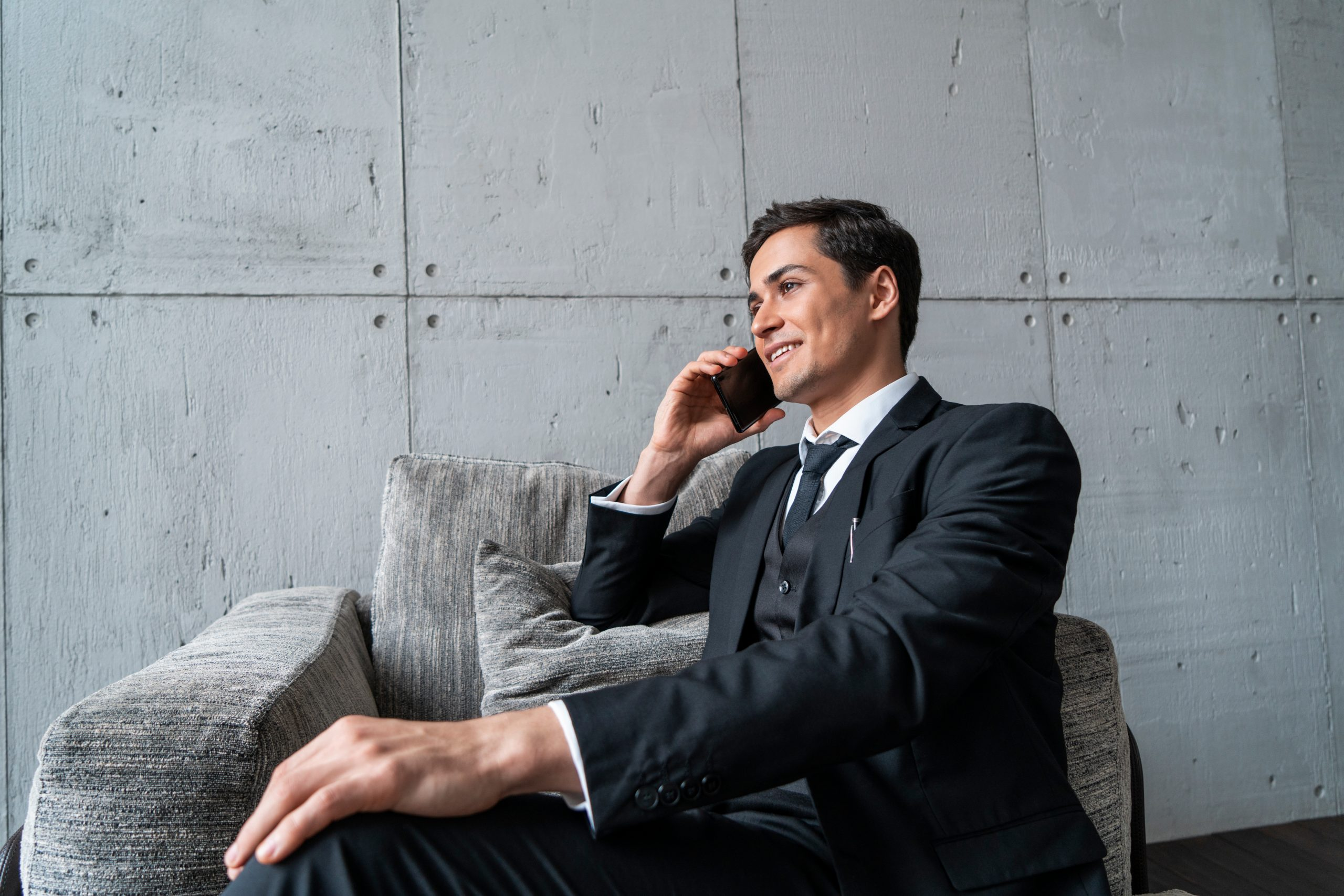 A suited businessman talking happily on the phone and sitting simply on a gray sofa chair