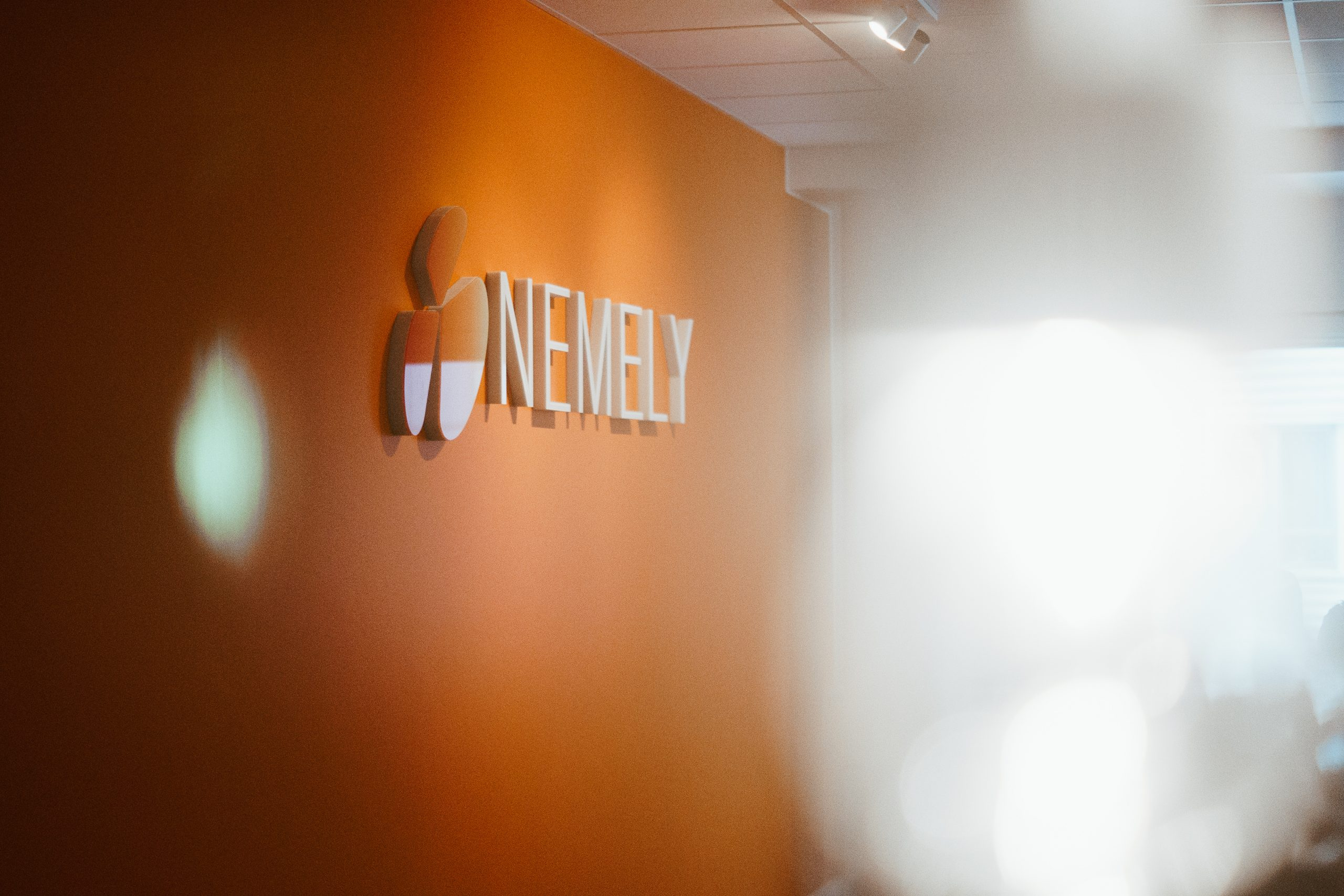 Orange mural wall that has the name and logo of Nemely at its office in Stockholm