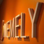 Nemely logo on an orange mural wall at the Stockholm office