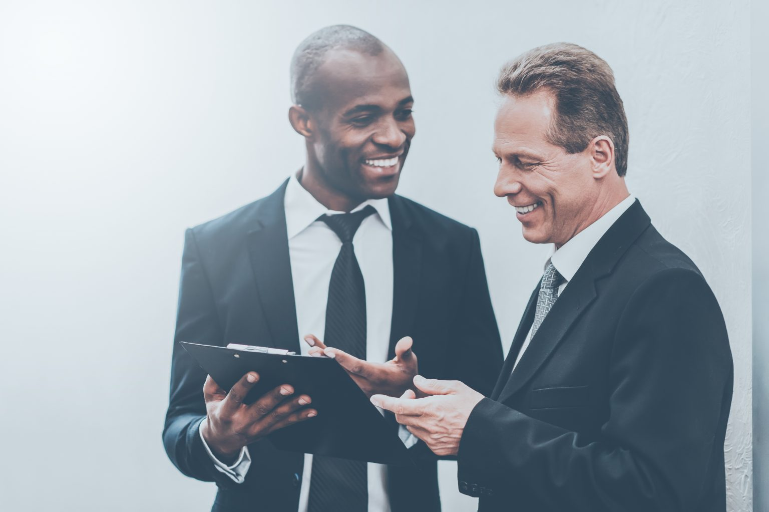 Smiling businessmen with a good relationship discussing and looking at a B2B sales report on a clipboard